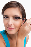 Young woman applying mascara on her lashes