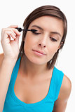Young woman almost closing her eyes while applying mascara