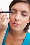 Young woman using an eye pencil to apply make-up