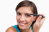 Young female using an eyebrow pencil to make-up