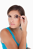 Beautiful teenager putting eyeshadow on her eyelid