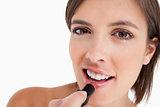 Smiling teenage girl applying make-up while putting on lipstick