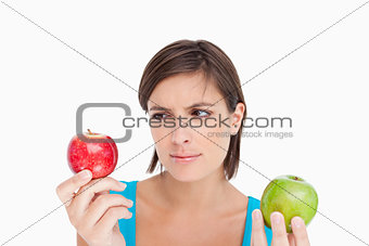Teenage holding two apples and looking at the red one