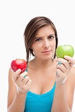 Serious teenage girl holding a green and a red apple