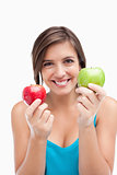 Smiling young woman holding two apples