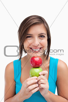 Teenager smiling and holding two apples between her hands and he