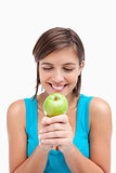 Smiling teenager looking at a green apple placed on her hands cr