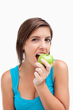 Attractive teenager eating a green apple