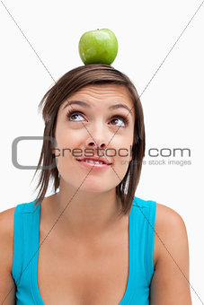 Attractive young woman standing upright with a green apple on he
