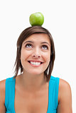 Smiling teenage girl trying to look at a green apple placed on h