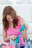 Young woman looking at her new blue swimsuit