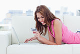 Young woman looking at her credit card to make purchases on inte