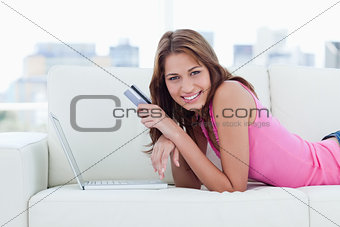 Young smiling woman lying on a comfortable sofa in front of her