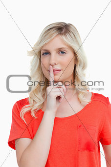 Beautiful woman looking at the camera while telling to be quiet