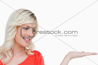 Smiling woman looking at her hand palm up