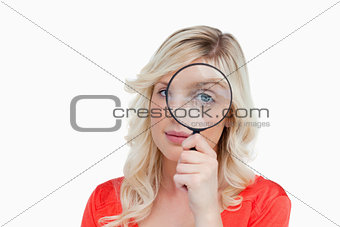 Fair-haired woman looking through a magnifying glass