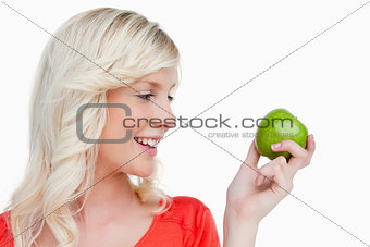 Young blonde woman looking on the side while holding a green app