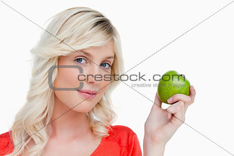 Attractive woman holding a green apple while looking at the came