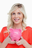 Smiling teenage girl holding a pink piggy bank in her hands