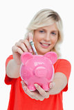 Young blonde woman putting notes into a pink piggy bank