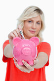Piggy bank receiving notes and held by a young woman