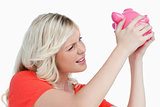 Fair-haired woman shaking a pink piggy bank