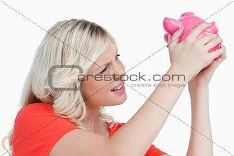 Fair-haired woman shaking a pink piggy bank