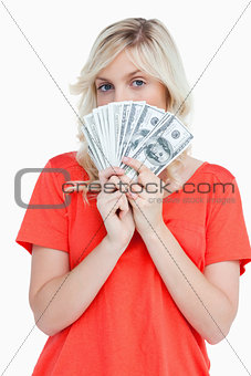 Attractive woman hiding her face behind dollar bank notes