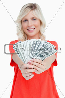A fan of dollar notes held by a smiling attractive woman