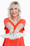Smiling woman holding a fan of dollar notes in her hands