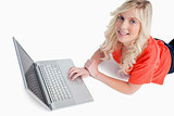 Smiling young woman using her laptop while lying down