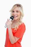 Young blonde woman smiling while singing into a microphone