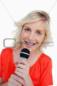 Smiling teenager singing in a cordless microphone