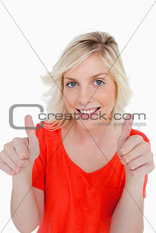 Teenage girl showing her thumbs up and a beaming smile