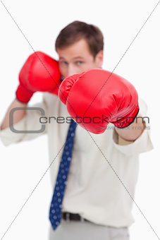 Attacking businessman with boxing gloves