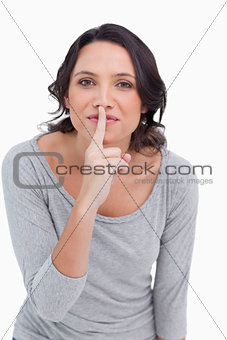 Close up of young woman asking for silence