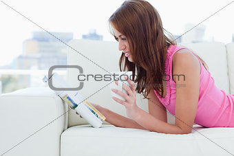 Young woman holding a cup of coffee while reading a magazine