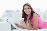 Young woman showing a great smile while reading and drinking cof