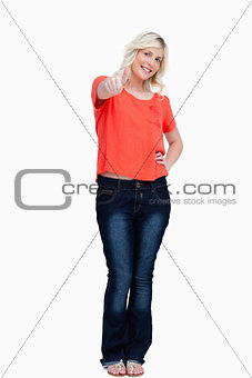 Smiling teenager tiltiing her head while showing her thumbs up