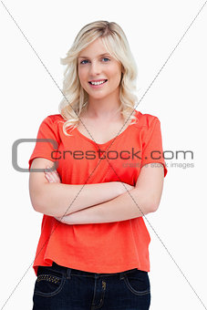 Smiling teenager crossing her arms against a white background