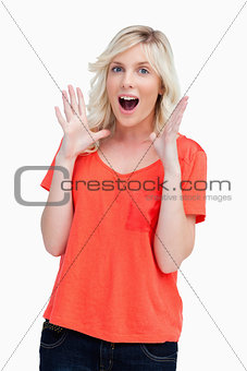 Surprised teenager standing upright with her arms next to her he