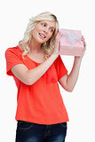 Smiling young woman looking at a gift while holding it