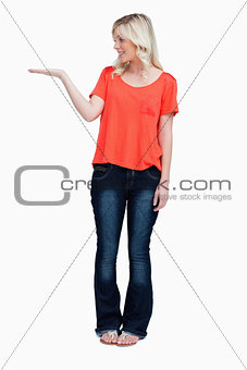 Smiling teenager standing upright with her hand palm up