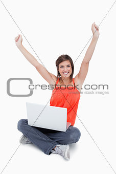 Attractive young woman sitting cross-legged and raised arms
