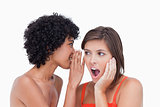 Teenager hearing a surprising secret from her friend