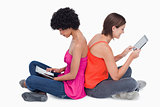 Teenage girl holding her tablet PC in the air while a friend is