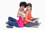 Laughing teenagers looking at a tablet PC while sitting cross-le