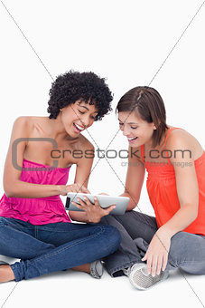 Teenage girl showing a funny application on her tablet PC to a f