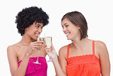 Young women clinking glasses of champagne while smiling