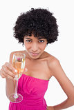 Young woman holding a glass of champagne while looking at the ca